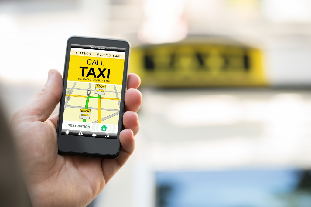 Close-up Of Person Booking Taxi On Smart Phone